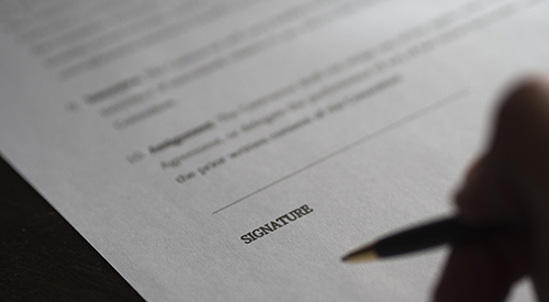 Photo of a person signing a document